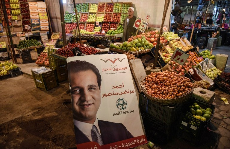 TO GO WITH AFP STORY BY JAY DESHMUKH - A poster showing Ahmed Mortada Mansour, Egyptian candidate for the liberal Free Egyptians Party for the parliamentary elections, is displayed at a market on October 9, 2015 in the capital Cairo. Egyptians begin voting on October 18, 2015 for a new 596-member parliament, the first since the previous assembly was dissolved in June 2012. The liberal Free Egyptians Party, founded by telecoms tycoon Naguib Sawiris -- who has offered to buy an island off Greece or Italy to shelter people fleeing from war ravaged Syria -- has 231 candidates contesting across Egypt's 27 provinces.   AFP PHOTO/ MOHAMED EL-SHAHED