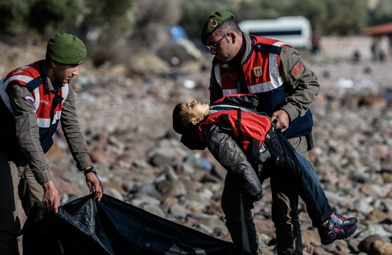 EDITORS NOTE: Graphic content / A Turkish gendarme carries the body of a migrant child on beach in Canakkale's Bademli district on January 30, 2016 after at least 33 migrants drowned when their boat sank in the Aegean Sea while trying to cross from Turkey to Greece, Turkey's state-run Anatolia news agency reported.   The migrants, who included those from Myanmar, Afghanistan and Syria, set sail from the Canakkale province to reach the nearby Greek island of Lesbos, Anatolia said.  / AFP / OZAN KOSE
