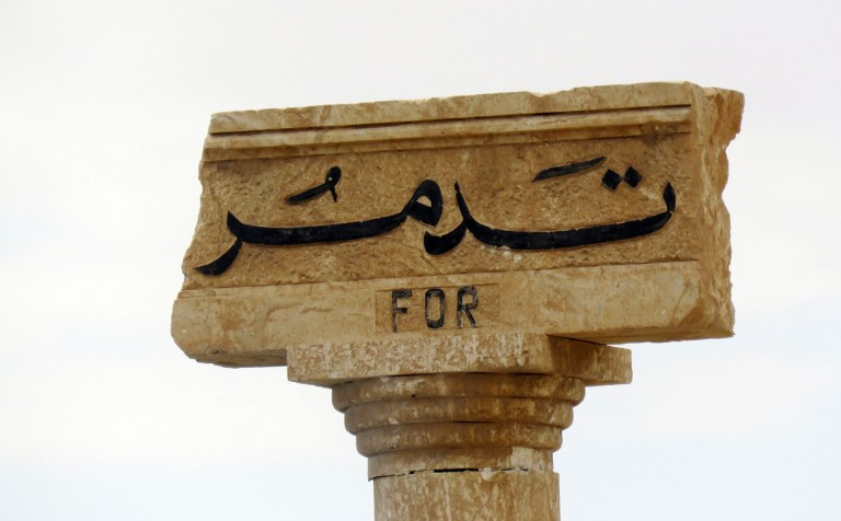 A picture shows the carved name of the city of 'Tadmor' (Palmyra) on a stone at the entrance of the historical city in central Syria on March 29, 2016. Regime troops were locked in heavy fighting with the Islamic State group in central Syria, where they dealt the jihadists a major blow by seizing the ancient city of Palmyra.   / AFP / STRINGER