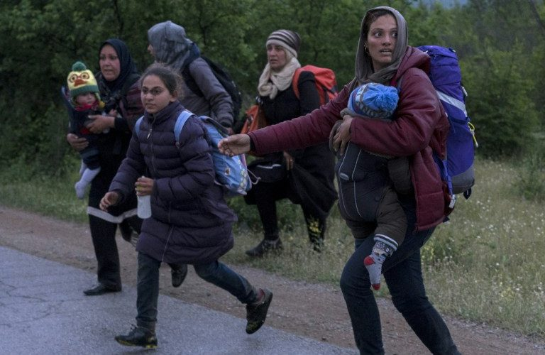 Syrian refugees cross a road with their children while on the run in a forest in Macedonia after illegally crossing Greek-Macedonian border near the city of Gevgelija on April 23, 2016. Some 50,000 people, many of them fleeing the war in Syria, have been stranded in Greece since the closure of the migrant route through the Balkans in February. / AFP PHOTO / JOE KLAMAR