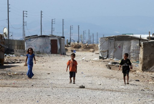 "Syrian refugee children walk at an unofficial refugee camp in the area of Arida, north of Beirut, on June 15, 2015. Rights group Amnesty International slammed world leaders for ""condemning millions of refugees to an unbearable existence"" and demanded they work closely to resolve the ""worst crisis"" since World War II.  AFP PHOTO / JOSEPH EID / AFP PHOTO / JOSEPH EID"