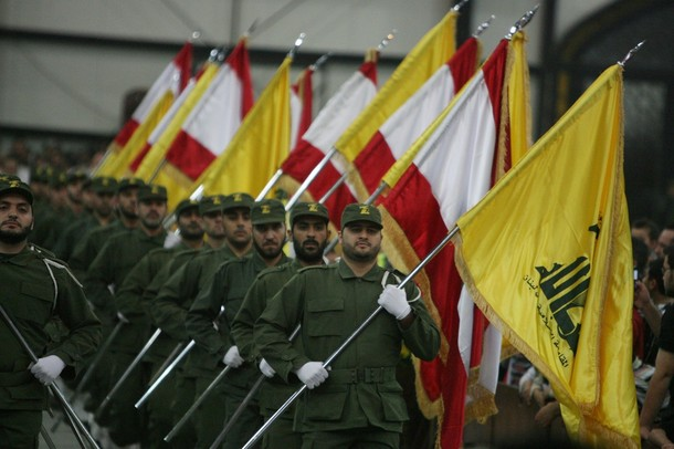 Hezbollah fighters, holding up national flags and the yellow flag of the militant Shiite Muslim group, parade on the occasion of Martyr's Day in the southern suburbs of Beirut November 11, 2009. Lebanon's incoming Prime Minister Saad Hariri announced earlier this week the new cabinet line-up after nearly five months of tough negotiations with his rivals in the Iran- and Syria-backed Hezbollah-led alliance.  AFP PHOTO/RAMZI HAIDAR (Photo credit should read RAMZI HAIDAR/AFP/Getty Images)